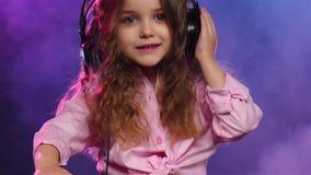 Liten flicka i hörlurarlekar för dj-konsol långsam rörelse arkivfilmer