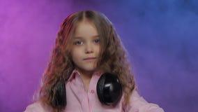 Liten flicka i hörlurarlekar för dj-konsol rökig bakgrund stock video