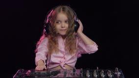 Liten flicka i hörlurarlekar för dj-konsol Svart bakgrund lager videofilmer