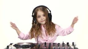 Liten flicka i hörlurarlekar för dj-konsol Vit bakgrund stock video