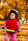 Liten flicka i hjälm på cykeln Fotografering för Bildbyråer