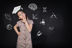 Liten flicka i imaginärt avläggande av examenlock som tänker om skola Arkivfoto