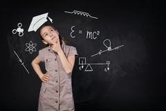 Liten flicka i imaginärt avläggande av examenlock som tänker om skola Royaltyfria Foton