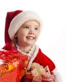 Liten flicka i julhatt med gåvaaskar Arkivbild