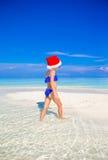 Liten flicka i jultomtenhatt på stranden under Arkivbilder