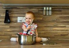Liten flicka i köket med en slev och en kruka royaltyfria foton