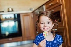 Liten flicka i köket som ler som äter klubban Arkivfoton