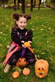liten flicka i karnevaldräkt med pumpa som firar halloween fotografering för bildbyråer