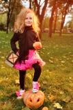 liten flicka i karnevaldräkt med pumpa som firar halloween royaltyfri bild