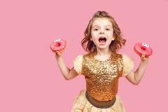 Liten flicka i klänning med donuts Royaltyfri Bild