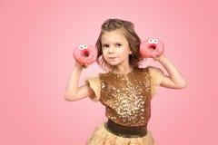 Liten flicka i klänning med donuts Fotografering för Bildbyråer