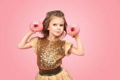 Liten flicka i klänning med donuts Arkivfoto