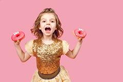 Liten flicka i klänning med donuts Royaltyfria Bilder