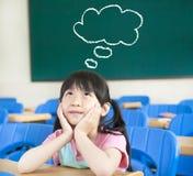 Liten flicka i klassrumet med tänkande Arkivfoton