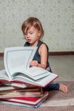 liten flicka i mörker - blått klänningläseboksammanträde på golvet nära nallebjörn Barnet läser berättelsen för leksak Vänder sid Royaltyfri Foto