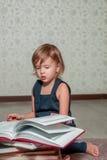 liten flicka i mörker - blått klänningläseboksammanträde på golvet nära nallebjörn Barnet läser berättelsen för leksak Vänder sid Arkivfoto
