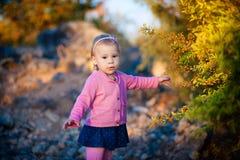 Liten flicka i orange bär för en rosa omslagshandlagpenna på busken Royaltyfri Fotografi