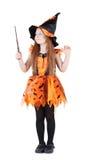 Liten flicka i orange dräkt av häxan för Halloween Arkivfoton