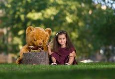 Liten flicka i parkera med en nallebjörn Fotografering för Bildbyråer