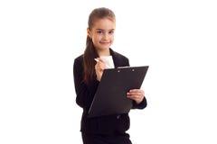 Liten flicka i penna och mapp för svart omslag hållande Fotografering för Bildbyråer