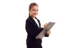 Liten flicka i penna och mapp för svart omslag hållande Royaltyfri Foto