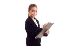 Liten flicka i penna och mapp för svart omslag hållande Royaltyfria Foton