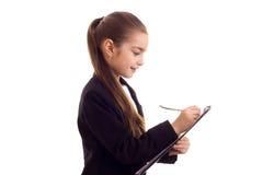 Liten flicka i penna och mapp för svart omslag hållande Arkivbild