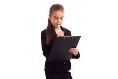 Liten flicka i penna och mapp för svart omslag hållande Royaltyfri Bild