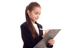 Liten flicka i penna och mapp för svart omslag hållande Royaltyfri Fotografi