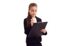 Liten flicka i penna och mapp för svart omslag hållande Arkivfoto