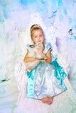 Liten flicka i prinsessaklänning på en bakgrund av en vinterfe royaltyfria bilder