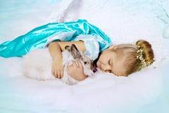Liten flicka i prinsessaklänning på en bakgrund av en vinterfe royaltyfria foton