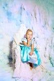 Liten flicka i prinsessaklänning på en bakgrund av en vinterfe Arkivfoto