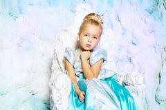 Liten flicka i prinsessaklänning på en bakgrund av en vinterfe Royaltyfri Fotografi