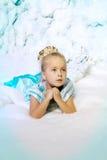 Liten flicka i prinsessaklänning på en bakgrund av en vinterfe Royaltyfri Foto