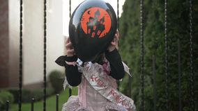 Liten flicka i prinsessan Costume Holding en svart ballong Hon ser j?tteglad, d?rf?r att idagen ?r allhelgonaaftonferie arkivfilmer