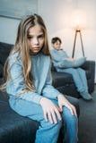 Liten flicka i pyjamas som ser kameran medan sammanträde för liten broder bakom Arkivbild