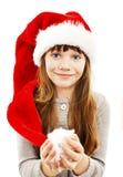 Liten flicka i röd jultomtenhatt. Stående arkivfoto