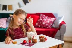 Liten flicka i röd klänning som äter julkakor med kakao i kopp, röda Chirstmas garneringar omkring royaltyfri fotografi