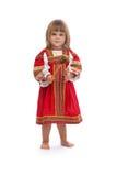 Liten flicka i röd traditionell klänning med en träsked Royaltyfri Bild