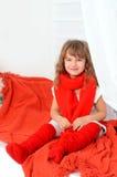 Liten flicka i rött och vitt inomhus royaltyfri foto
