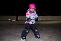 Liten flicka i rosa färger i hockeykugghjul arkivbild