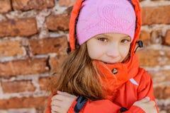Liten flicka i rosa hatt och omslag royaltyfria foton