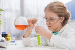 Liten flicka i skyddsglasögon med agens i flaskor i laboratorium Royaltyfria Foton