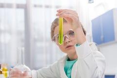 Liten flicka i skyddsglasögon med agens i flaskor i laboratorium Royaltyfri Fotografi