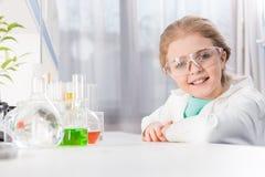Liten flicka i skyddsglasögon med flaskor i laboratoriumet som ser kameran Royaltyfria Bilder