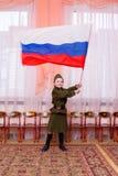 Liten flicka i sovjetisk vinkande flagga för militär likformig royaltyfri fotografi