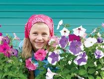 Liten flicka i trädgård på bakgrund av turkosstaketet Arkivbilder