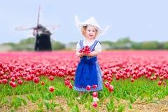 Liten flicka i tulpanfält med väderkvarnen i holländsk dräkt Arkivfoto