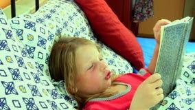 Liten flicka i underlag Flickan ser en gammal faderdagbok Den lilla flickan ser en gammal bok i säng Zoomkamerarörelse arkivfilmer